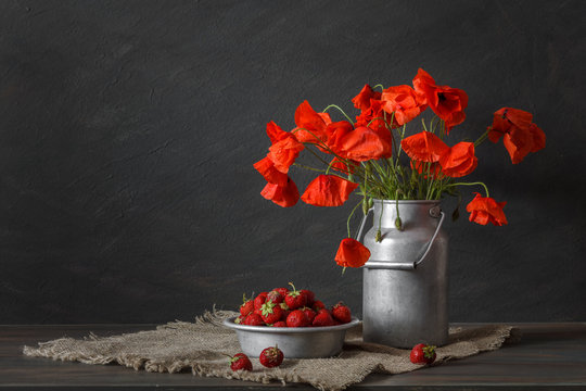 Still life in a rustic style: aluminum cookware, bouquet of red poppies and strawberry on a wooden table.
