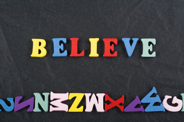 BELIEVE word on black board background composed from colorful abc alphabet block wooden letters, copy space for ad text. Learning english concept.