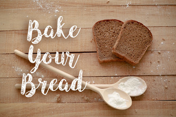 Slices of black bread on wooden background with Bake your bread sign on it