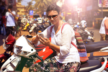 Woman in sunglasses sitting on motorcycle