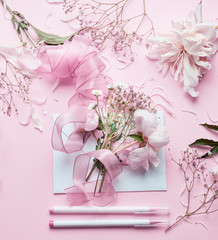 Lovely pink Florist workspace. Beautiful flowers, envelop ,ribbon and markers pencil on pastel background, top view. Creative  Invitation and holiday concept