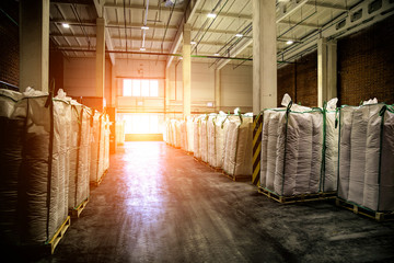 Hangar warehouse with big white polyethylene bags of industrial and logistics companies. Warehousing on the floor