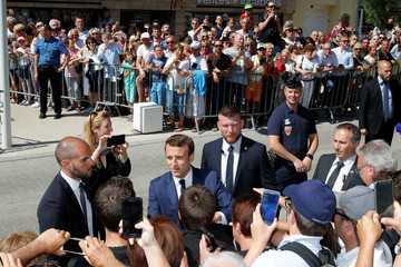 French President Emmanuel Macron greets supporters as he leaves his home to vote in parliamentary elections in Le Touquet