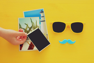 Hipster yellow sunglasses and funny moustache next to blank photographs