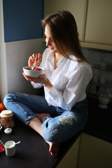 Young woman eating healthy breakfast ,sitting in kitchen, food, granola, lifestyle, beries