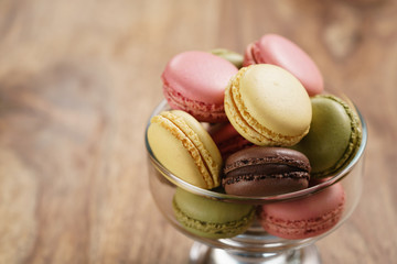 assorted macarons in glass bowl on wood table, closeup
