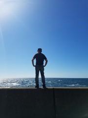 防波堤に立つ男性のシルエット