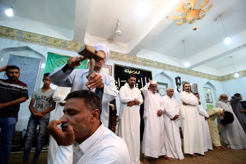 Iraqi Dervish has his head hit during a religious ritual to mark the holy month of Ramadan at their Tekiyah, a place of worship