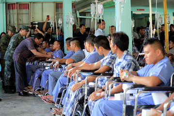 Philippines' President Duterte awards a medal and cash money to a wounded soldier from among government troops fighting against insurgents of the Maute group during his visit to the military camp hospital in Cagayan De Oro