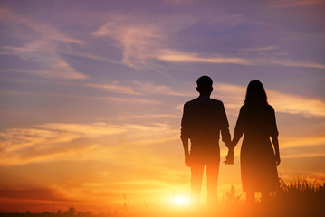 young couple is holding hands on a background sunset silhouette