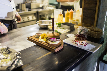 Two mouth-watering, delicious homemade burger used to chop beef. on the wooden table. The burgers are inserted knives.