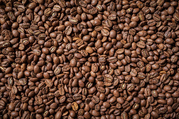 Roasted brown coffee beans, top view background