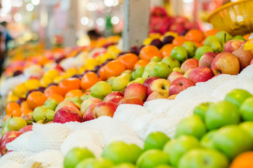 beautiful color combination, variety of fresh raw fruits background display at market stall.