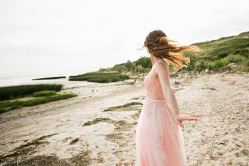 bride in a wedding dress is walking along the beach.