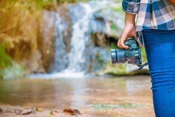 close up of camera with  woman tourist on the background of waterfall