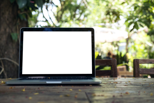 Mockup image of laptop with blank white screen on vintage wooden table in nature outdoor park