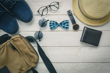 Top view accessories to travel with man clothing concept. bow tie,wallet on wooden background.watch,sunglasses,bag,hat and shoes on wood table.