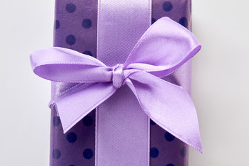 Cropped picture of gift box. Purple ribbon on violet box, white background.