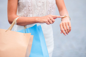 Close-up stylish woman stands with shopping bags and shows forefinger on watch outdoor