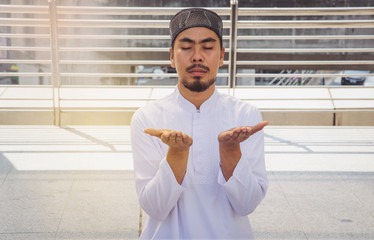 Religious muslim man praying in city