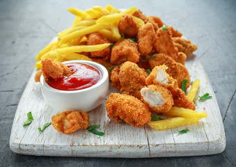 Fried crispy chicken nuggets with french fries and ketchup on white board Wall mural