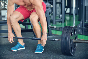 Man at the gym. Man makes exercises with barbell
