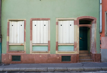 Pastel green and dark brown building with white windows and door beside the street in Colmar, France