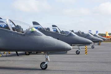 Hawk jet fighters on the ground. Four aircraft on the airfield.