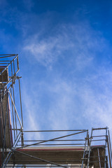 Scaffolding from bird's perspective in front of a blue sky