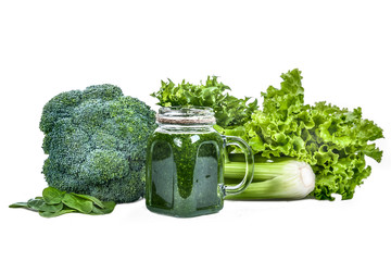 Green vegetables and smoothies from vegetables  isolated . Salad, broccoli, spinach, celery. Glass with green smoothies