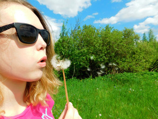 A girl wearing sunglasses is blowing dandelion