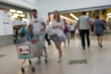 Abstract blurred background people shopping for diverse products in supermarket.