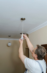 Electrician is installing a LED bulb.