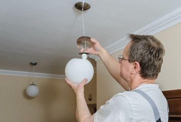 Electrician is instilling a ceiling lamp.