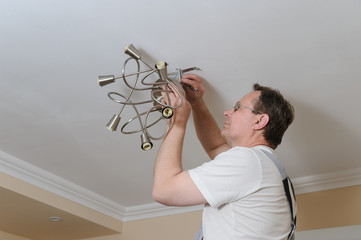 Electrician is installing and connecting a lamp.