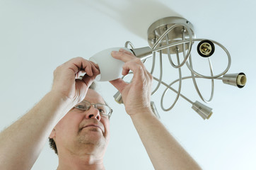 Electrician is attaching a chandelier.