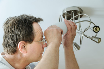 Electrician is installing a LED light bulb.