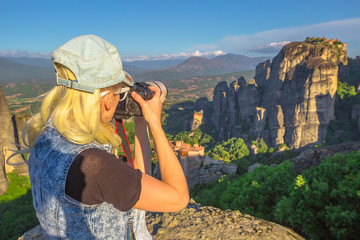 Traveler woman photographer with professional camera takes pictures of monasteries of Meteora in Central Greece, Europe. Caucasian female photographing a popular greek landmark. Europe travel.