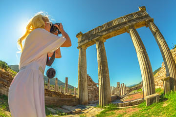 Travel woman photographer takes shot of Doric Propylon (entrance), Ancient Messene, Archaeological Site, Peloponnese, Greece. Caucasian female photographing a Greek Temple.Europe summer travel concept