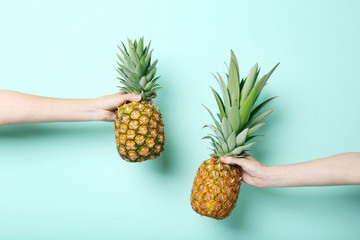 Female hands holding ripe pineapples on mint background