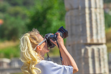 Portrait of travel woman photographer with professional camera in Ancient Messene, Archaeological Site, Peloponnese, Greece. Caucasian female take shot of a blurred ruins. Europe travel holidays.