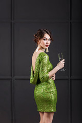 beautiful girl slim figure in a short green sparkly dress with open back is back on a dark grey background with a glass of champagne in hand close-up