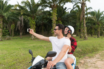 Couple Riding Motorbike, Man And Woman Taking Selfie Travel On Bike On Tropical Forest Road During Exotic Summer Holiday