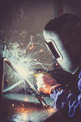 Worker with protective mask welding metal and producing smoke and sparks