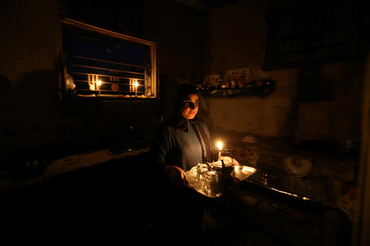 Palestinian girl holds tea inside the kitchen of her house during power cut in the southern Gaza Strip