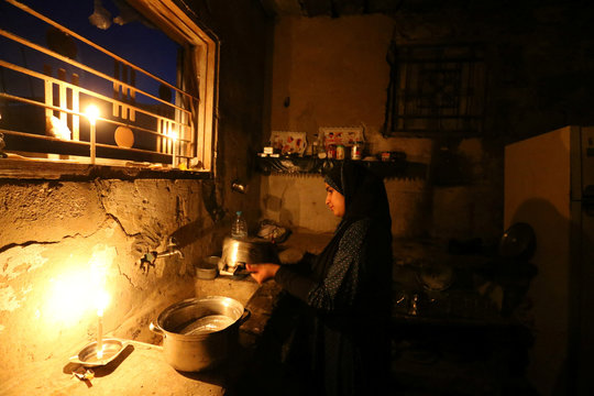 Palestinian girl cleans the kitchen of her house during power cut in the southern Gaza Strip