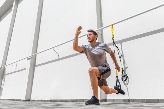 Fitness suspension straps man training legs with suspended lunge exercise at gym. Lower body workout.