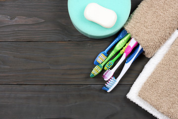 toothbrush tooth-brush with soap, bath towel and wisp of bast on wood background