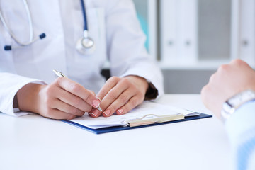 Female doctor filling medical form while consulting patient