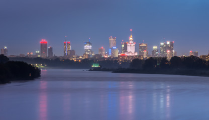 Colorful night panorama of Warsaw skyline, Poland, over Vistula river in the night
